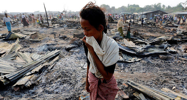 A woman walks among debris after fire destroyed shelters at a camp for internally displaced Rohingya Muslims in the western Rakhine State near Sittwe, Myanmar May 3, 2016. REUTERS/Soe Zeya Tun TPX IMAGES OF THE DAY